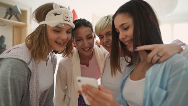 young girlfriends at a sleepover having fun while checking social media on the smart phone. - slumber party stock videos & royalty-free footage