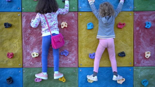 unga flickor klättrar en utomhus klättervägg - friklättring bildbanksvideor och videomaterial från bakom kulisserna