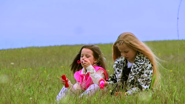 stockvideo's en b-roll-footage met young girls blowing bubbles. - blaas urinewegstelsel