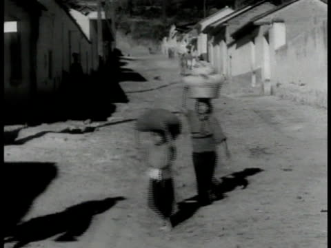 young girls crossing narrow street carrying bundle & basket on top of heads. - narrow stock videos & royalty-free footage