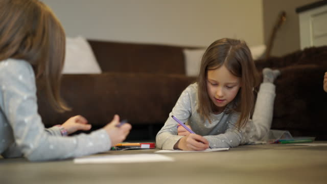 young girls drawing in living room