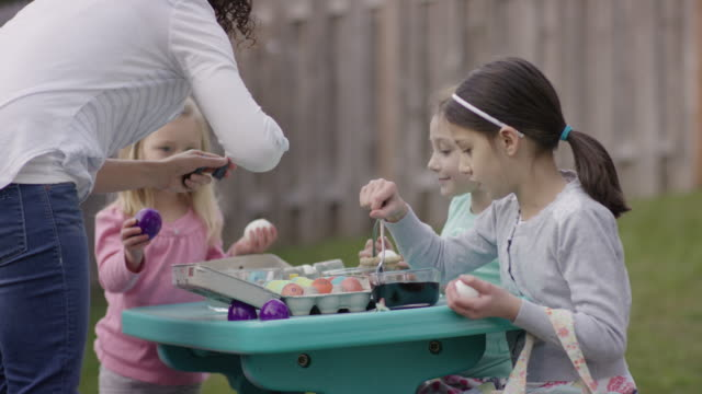 Young girls dying and coloring Easter eggs