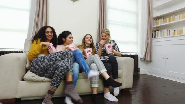 Young girls eating popcorns on sofa