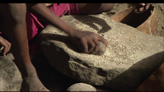 young girls grind grain on stone blocks, mali available in hd. - macinare video stock e b–roll
