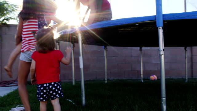 Junges Mädchen helfen einander Klettern auf einem Trampolin