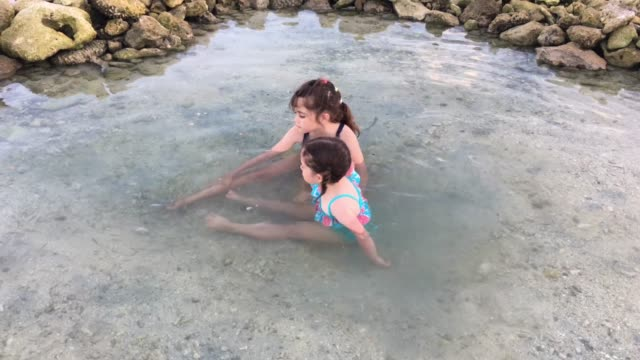 young girls in a rock pool cleaning their feet with garra rufa fish - rarotonga stock videos & royalty-free footage