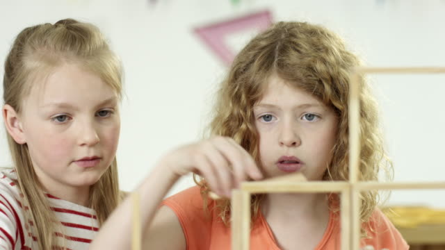 young girls in classroom - building bricks on desk - 30 sekunden oder länger stock-videos und b-roll-filmmaterial