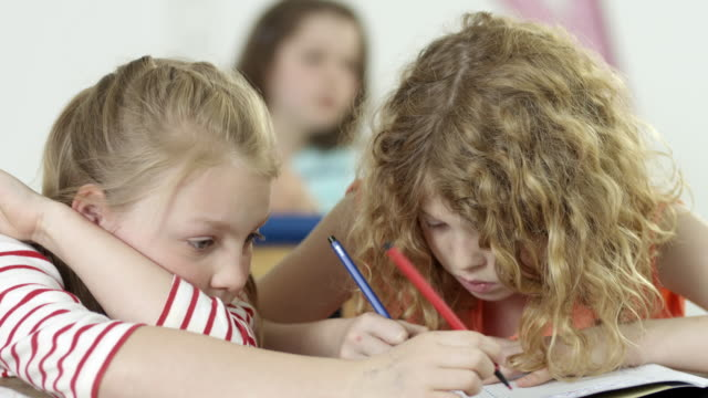 young girls in classroom - one girl is diverted