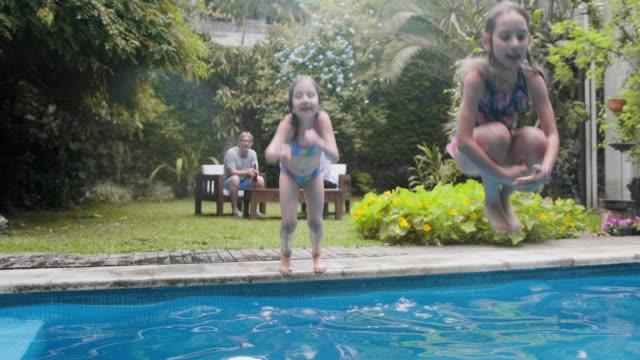 stockvideo's en b-roll-footage met jonge meisjes die in familiezwembad springen - 8 9 jaar
