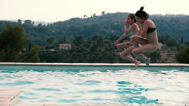 2 young girls jumping into the pool in extreme slow-motion