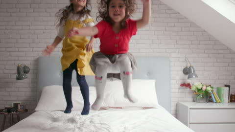 2 young girls jumping up and down on their bed and laughing - child stock videos & royalty-free footage