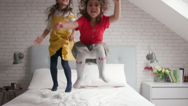 vídeos de stock e filmes b-roll de 2 young girls jumping up and down on their bed and laughing - criancas