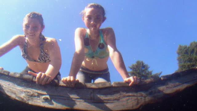 giovani ragazze guardano all'acqua di mare dock - sbirciare video stock e b–roll