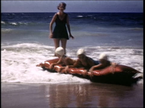 young girls playing in the ocean surf, they cling to an inflatable raft and sit in an inner tube. girls playing in surf on july 01, 1941 in california - reifenschlauch stock-videos und b-roll-filmmaterial