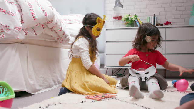 2 young girls playing together at home in their bedroom - mask disguise stock videos & royalty-free footage
