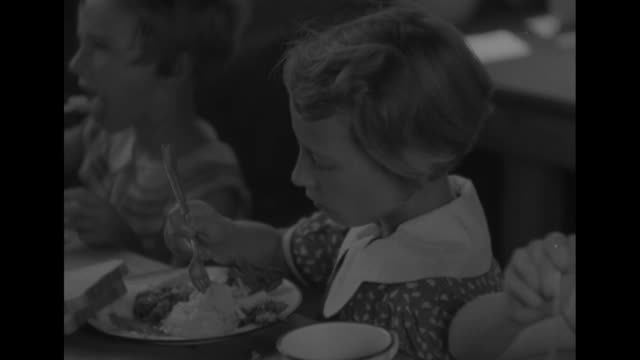 young girls sit on both sides of a long table, eating a meal / young girl uses large fork to eat some mashed potatoes; she breaks a piece of bread,... - マッシュポテト点の映像素材/bロール