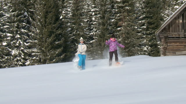 HD: Young girls snowshoeing through snowy landscape.