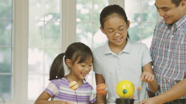 young girls studying astronomy while home schooling with their dad - fatcamera stock videos and b-roll footage