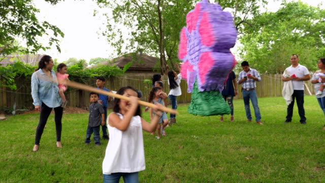 ms pan young girls taking turns trying to break open pinata during family birthday party - papier stock videos & royalty-free footage
