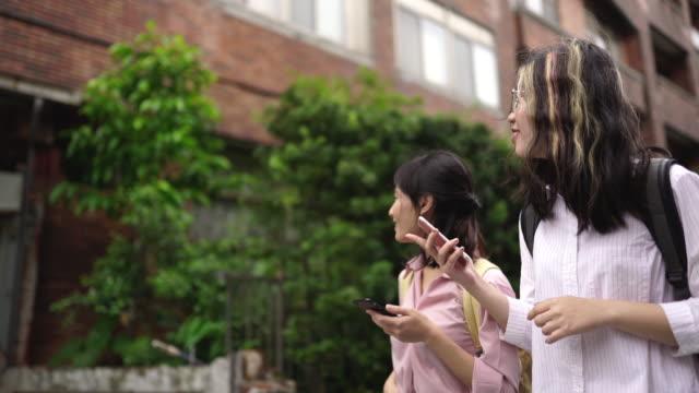 vidéos et rushes de jeunes filles utilisant le téléphone sur leur chemin à l'école - regarder autour de soi