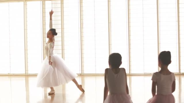 ws young girls watching a ballerina dance. - ballettstudio stock-videos und b-roll-filmmaterial
