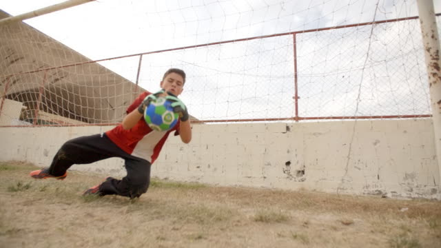 young goalkeeper dives to block shot at youth soccer practice - halten stock-videos und b-roll-filmmaterial
