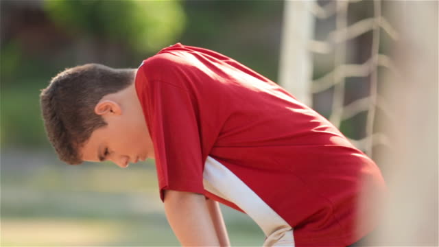 young goalkeeper stares at the ground and breathes heavily - solo un bambino maschio video stock e b–roll