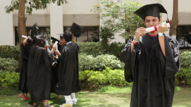 young graduates celebrating  - mortar board stock videos and b-roll footage
