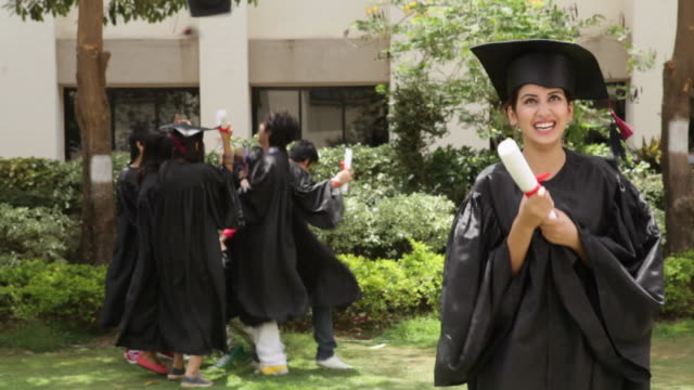 young graduates celebrating  - graduation gown stock videos and b-roll footage