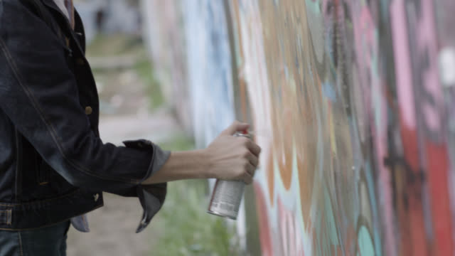 Young graffiti artist covers wall with spray paint