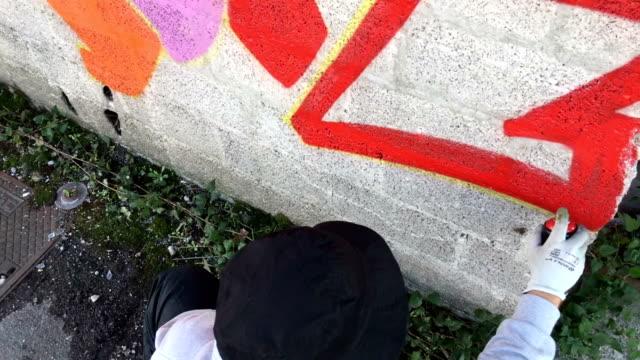 stockvideo's en b-roll-footage met jonge graffiti kunstenaar tekening graffiti op muur - graffiti