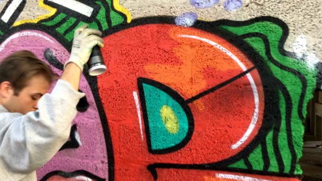 vídeos de stock e filmes b-roll de young graffiti artist drawing graffiti on wall - ocupação artística