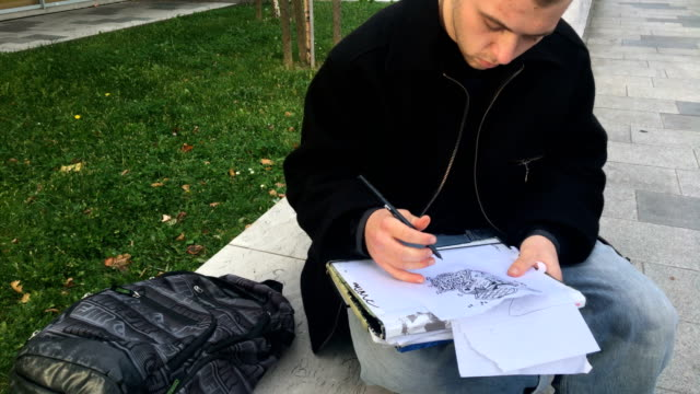 Young Graffiti Artist Drawing Sketches on City Street