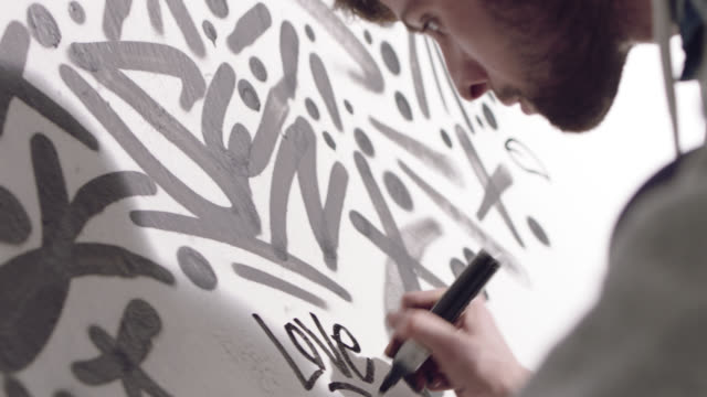 CU. Young graffiti artist writes LOVE on white wall with black marker.
