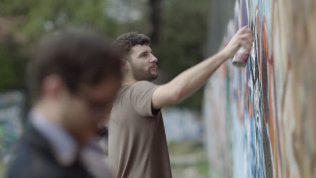 Young graffiti artists cover urban wall with spray paint