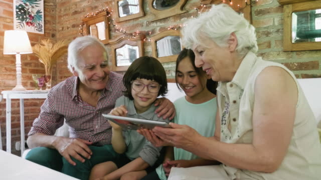 young grandchildren using digital tablet with grandparents - digital native stock videos & royalty-free footage