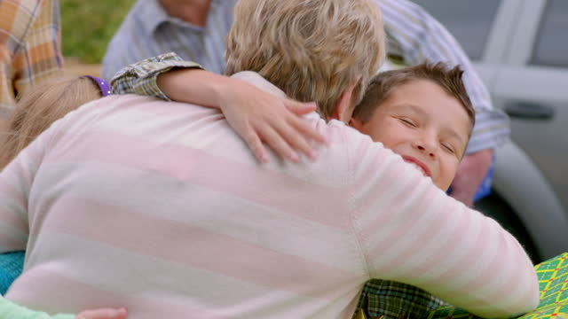 Young grandson carrying Christmas presents hugs grandmother