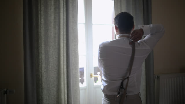 young groom dressing up for wedding day in hotel room. groom adjusting his suspenders - suspenders stock videos and b-roll footage