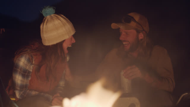 Young group of friends talk and laugh around flickering campfire at night.