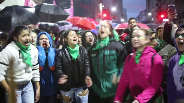 vidéos et rushes de a young group of legal abortion activists dance and sing slogans in front of the national congress building while senators vote for the new abortion... - argentine