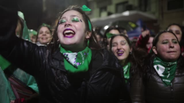 a young group of legal abortion activists dance and sing slogans in front of the national congress building while senators vote for the new abortion... - argentina stock videos & royalty-free footage