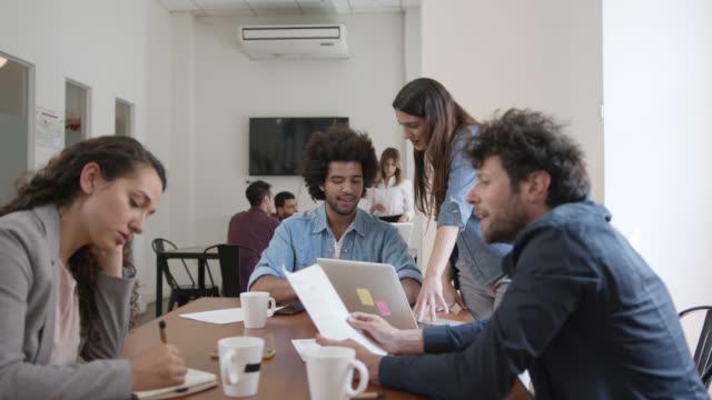 vídeos de stock, filmes e b-roll de grupo novo de povos em um escritório de coworking que discute o negócio que senta-se em uma mesa que usa a tecnologia - caneca