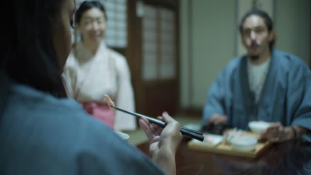 stockvideo's en b-roll-footage met jonge gast eten met eetstokjes in ryokan - ryokan