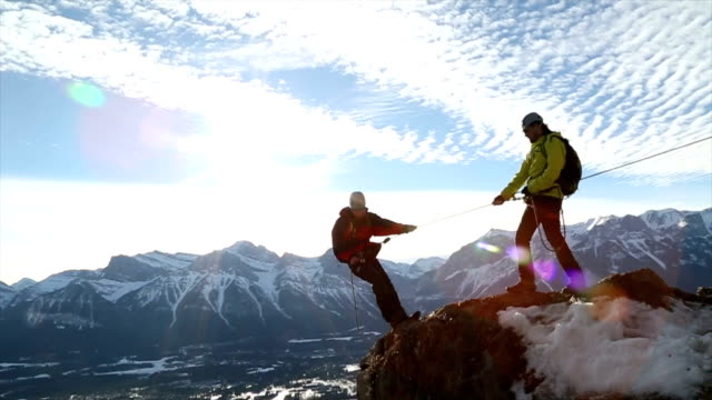 young guide belays friend on steep mountain ridge - vertrauen stock-videos und b-roll-filmmaterial