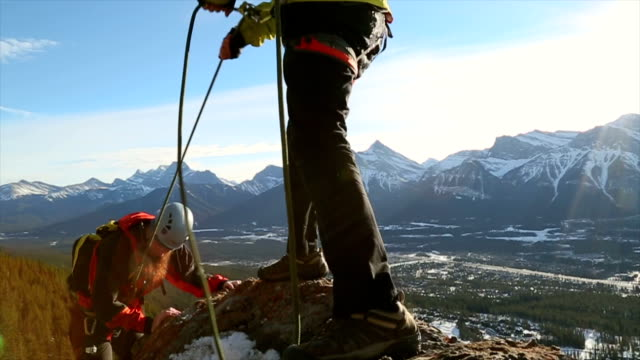 young guide belays friend on steep mountain ridge - male friendship stock videos and b-roll footage