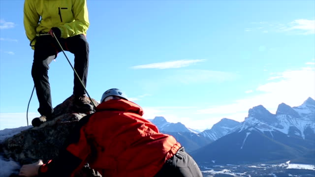 Young guide belays friend up steep mountain ridge