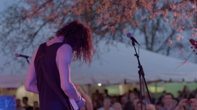 young guitarist headbangs as he rocks out with band at outdoor music festival - solo performance stock videos and b-roll footage