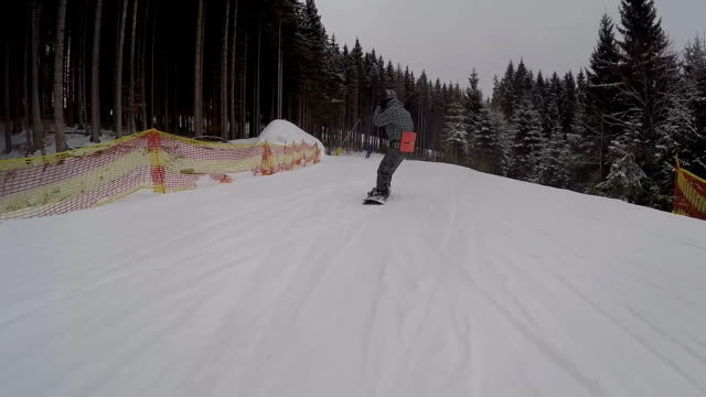 Young guy is snowboarding on the slopes in the сarpathians.