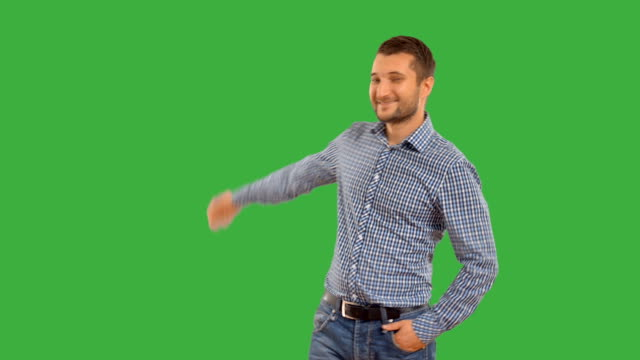 Young guy showing copy space on a green background