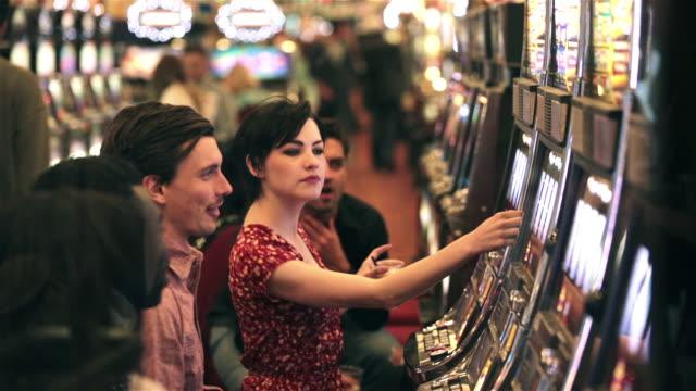 vídeos y material grabado en eventos de stock de young guy wins big at casino slot machine, celebrates with friends - máquina con ranura